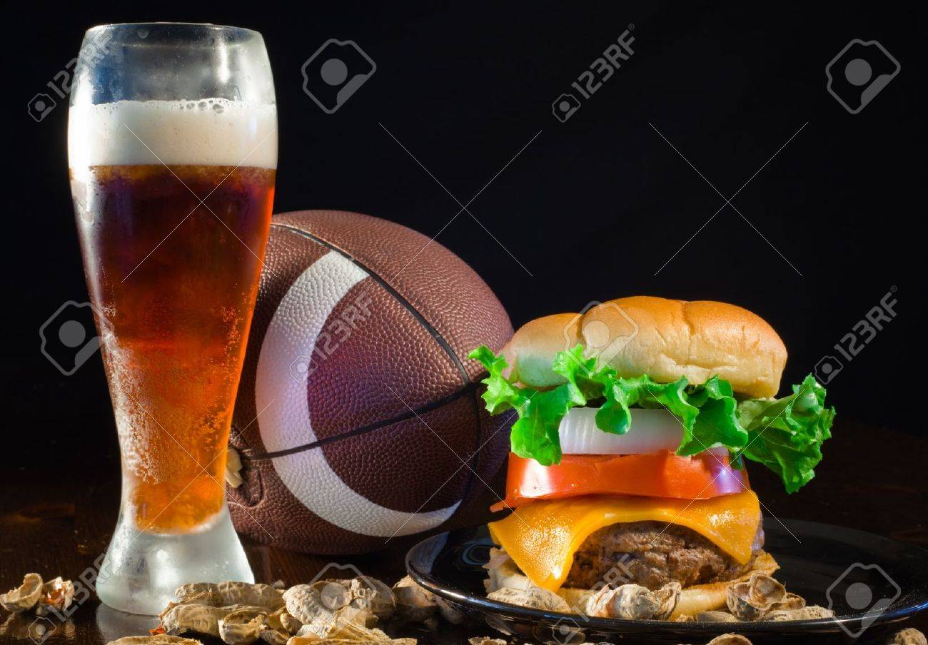 A close up of a big hamburger surrounded with peanuts, beer and a football. Banque d'images - 8750255