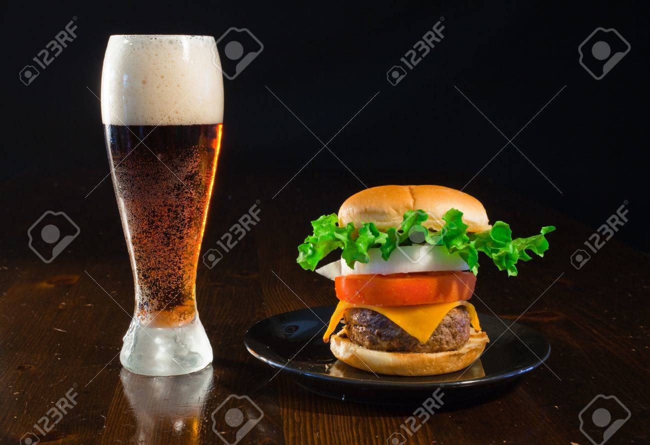 A close up of a big hamburger on a black plate with a cold amber beer. Banque d'images - 8750275