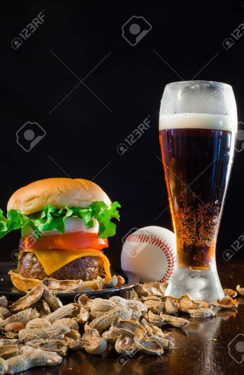 A close up of a big hamburger surrounded with peanuts, beer and a baseball ball. Stock Photo - 8750266