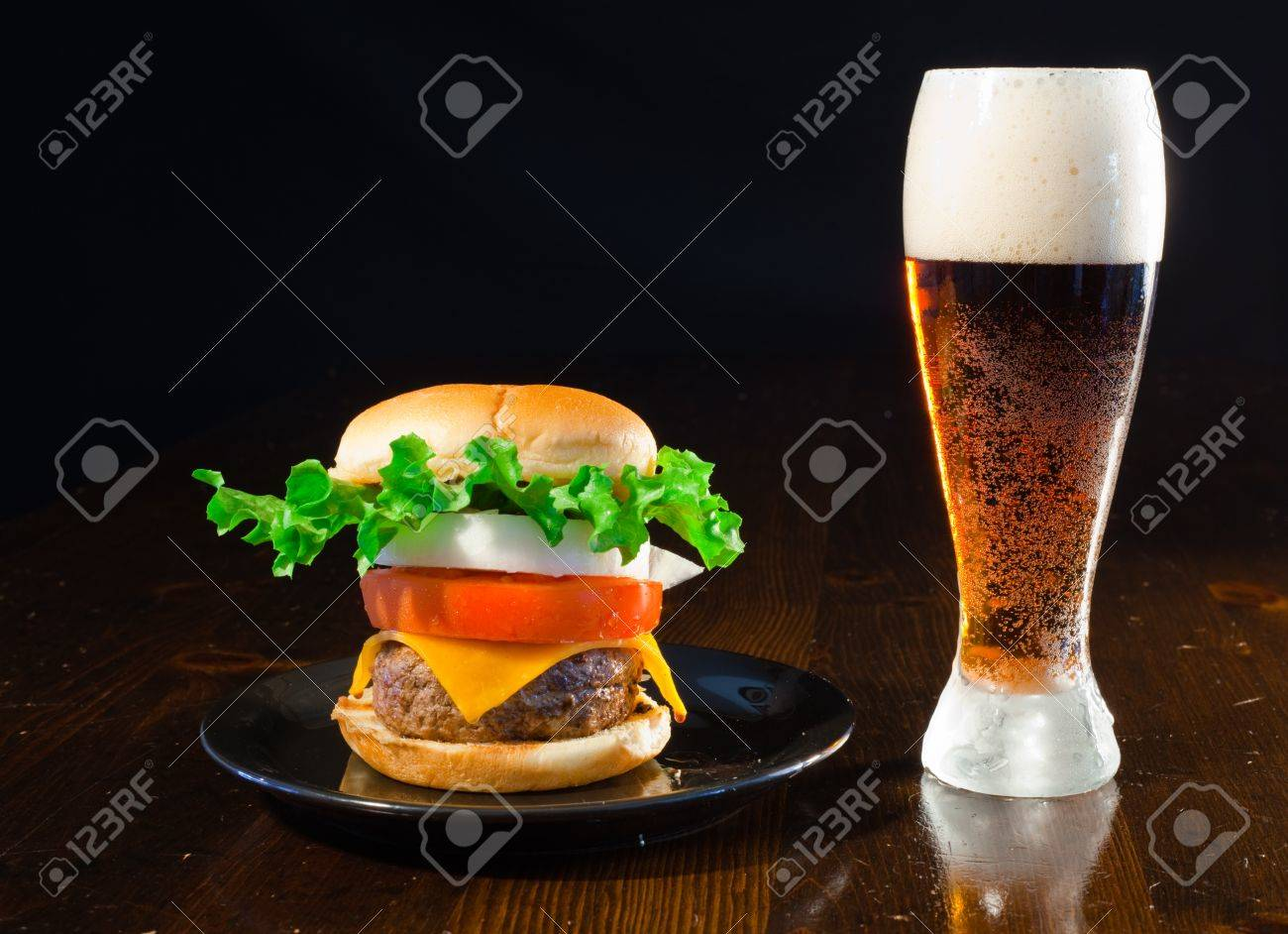 A close up of a big hamburger on a black plate with a cold amber beer. Banque d'images - 8750272