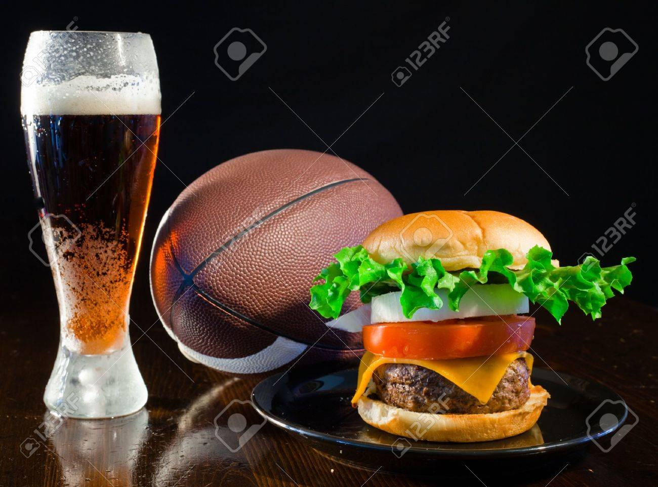A close up of a big hamburger on a black plate with a cold amber beer and a football. Banque d'images - 8750273