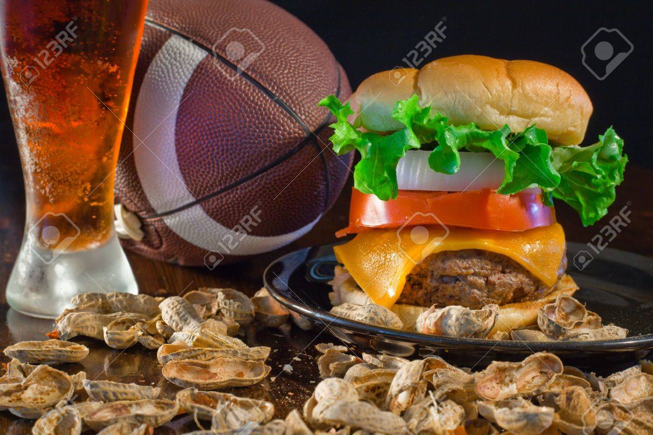 A close up of a big hamburger surrounded with peanuts, beer and a football. Banque d'images - 8750278
