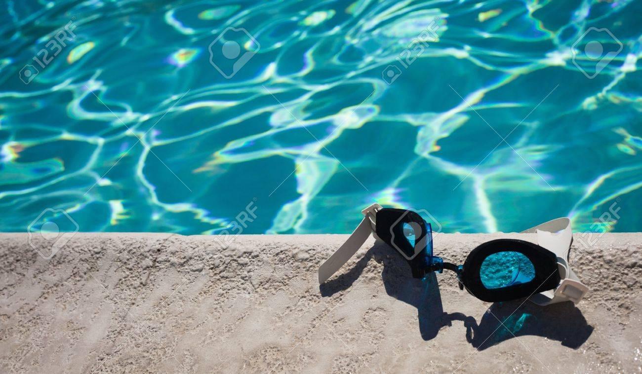 Un gros plan d'une paire de lunettes de natation pose sur le bord de la piscine. Banque d'images - 10010917