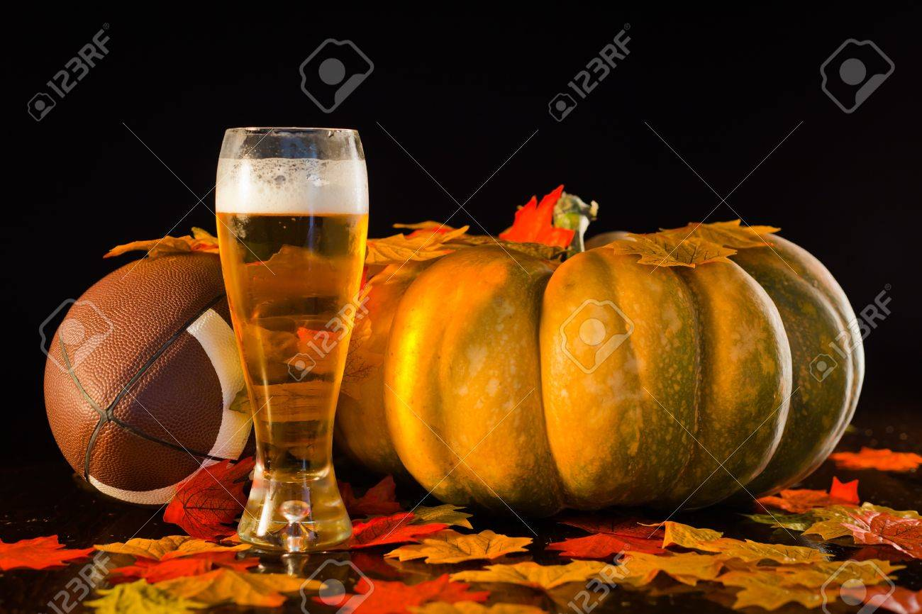 A studio shot of a pumpkin, football, leaves and a tall cold beer. Stock Photo - 10828438