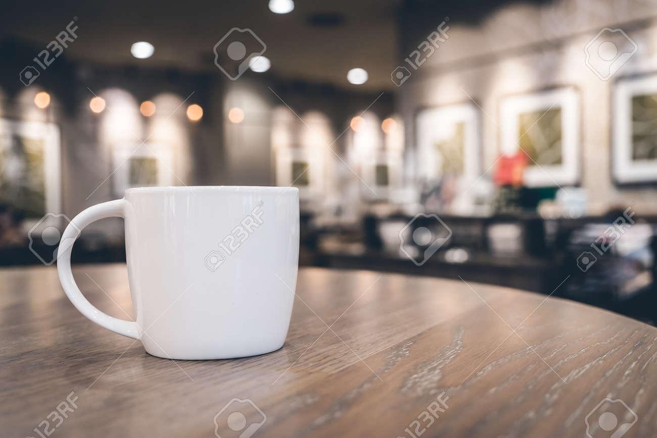 Soft focus op witte koffiekopje in coffeeshop café op oude houten