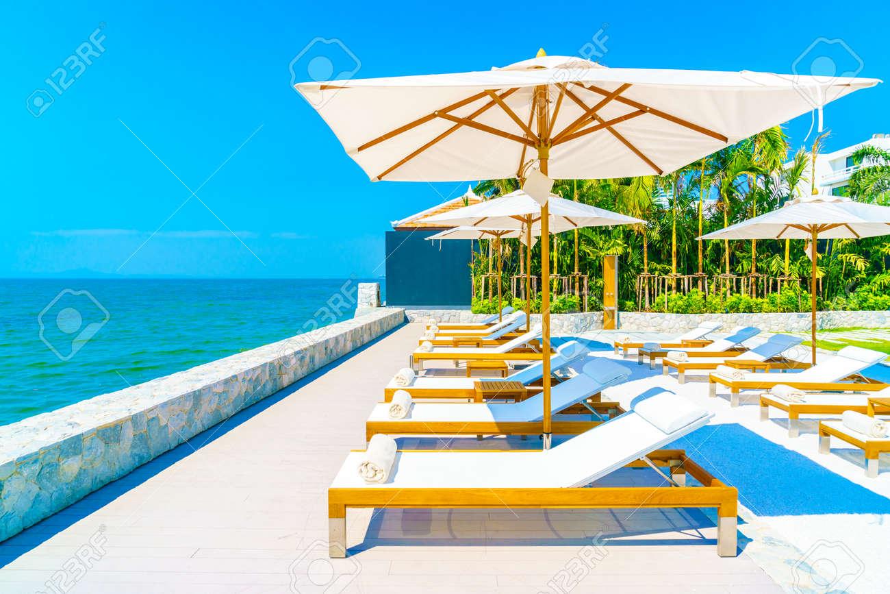 Beautiful luxury hotel swimming pool resort with umbrella and chair Standard-Bild - 51427605