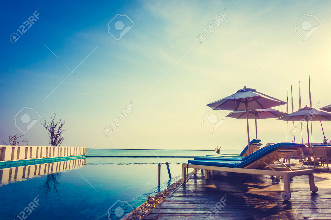 Beautiful luxury swimming pool in hotel resort with umbrella and chair in sunset times - Vintage Filter and Boost up color processing Standard-Bild - 51986278