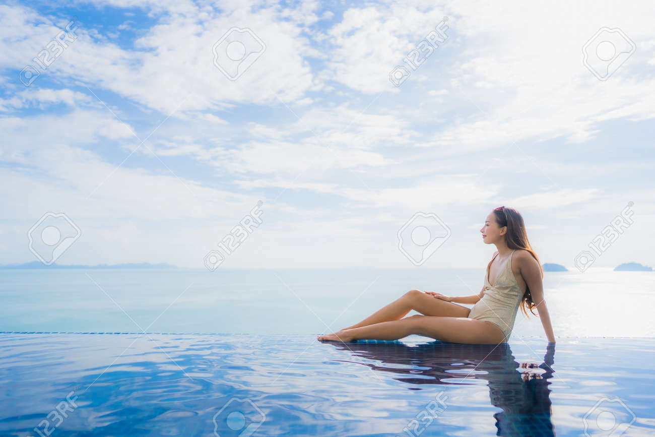 Portrait young asian woman relax smile happy around swimming pool in hotel and resort for holiday vacation travel concept - 126560152