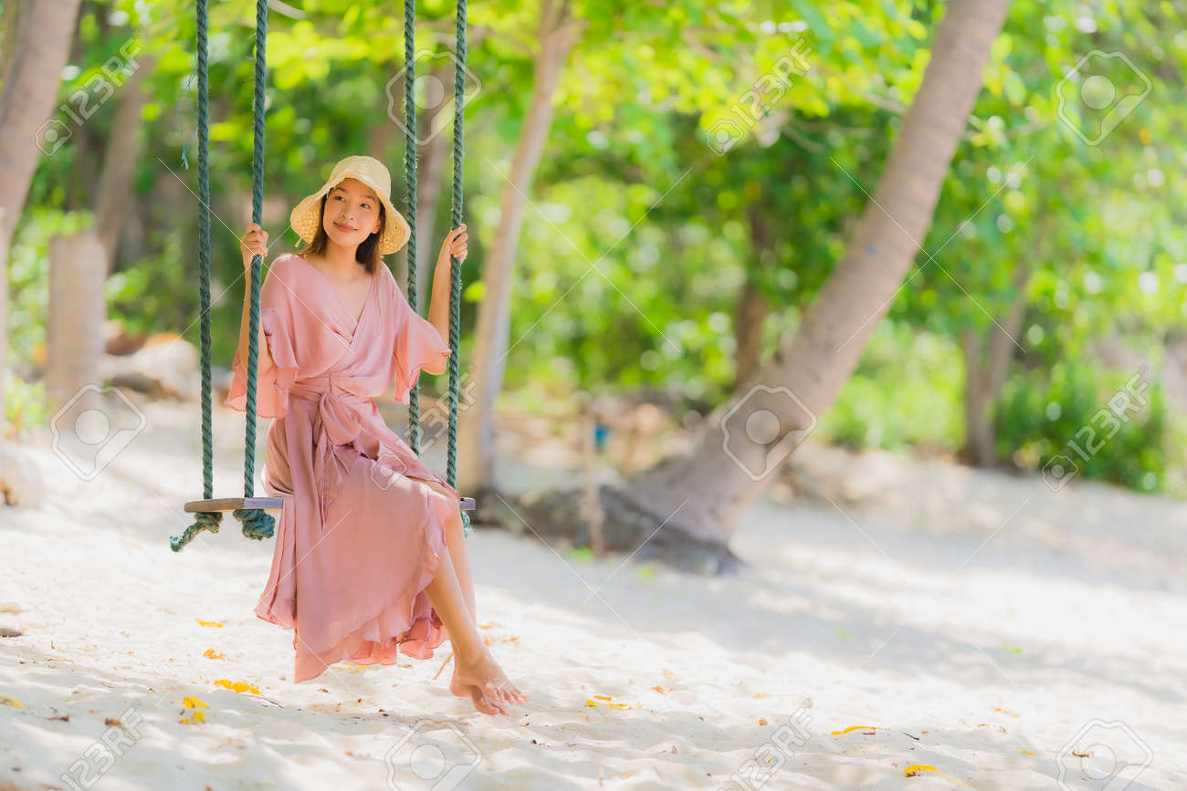 Portrait young asian woman sitting on swing rope and sea around beach sea ocean coconut palm tree for travel in holiday vacation concept - 126727361