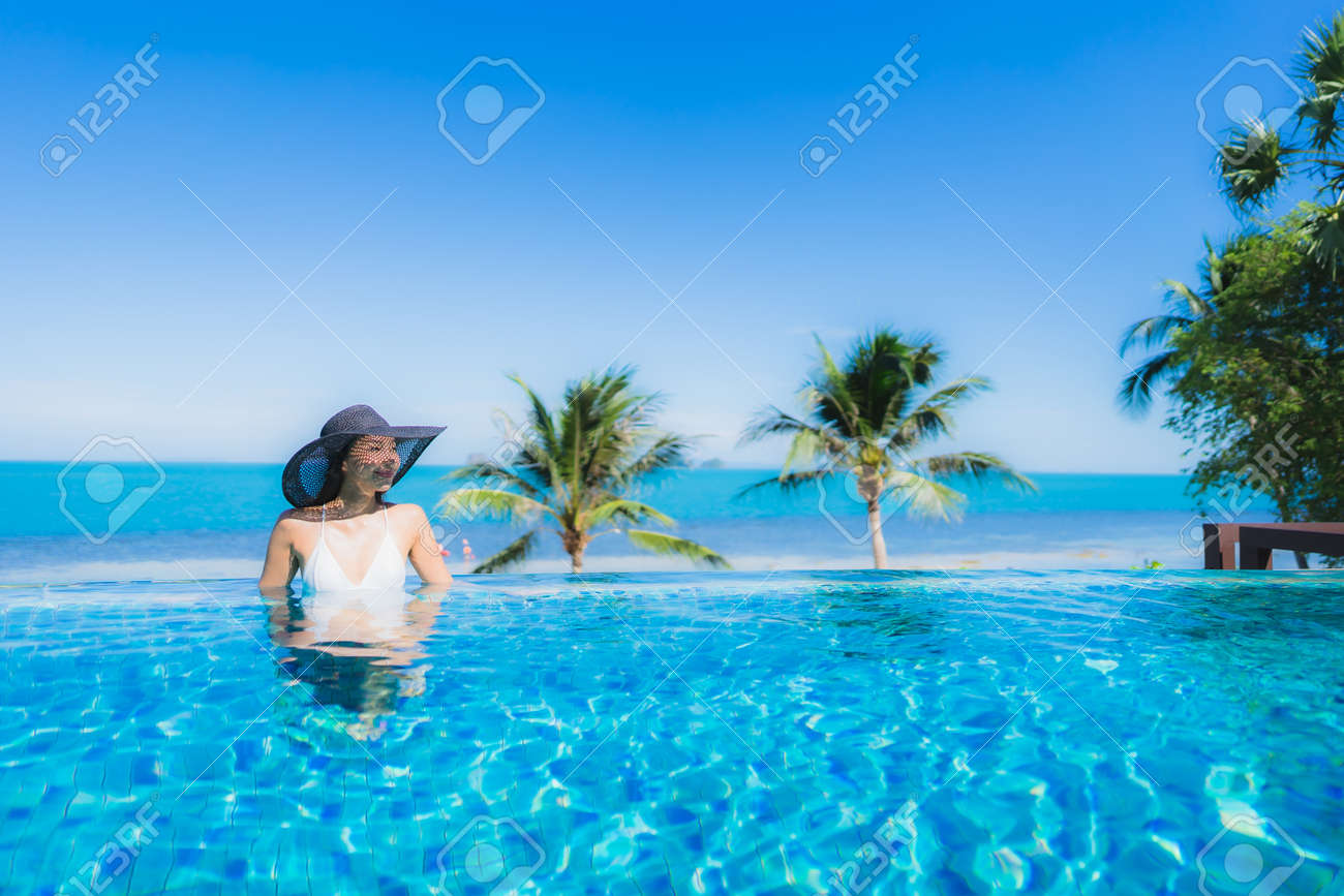Portrait beautiful young asian woman relax in luxury outdoor swimming pool in hotel resort nearly beach sea ocean for holiday vacation concept - 128805978