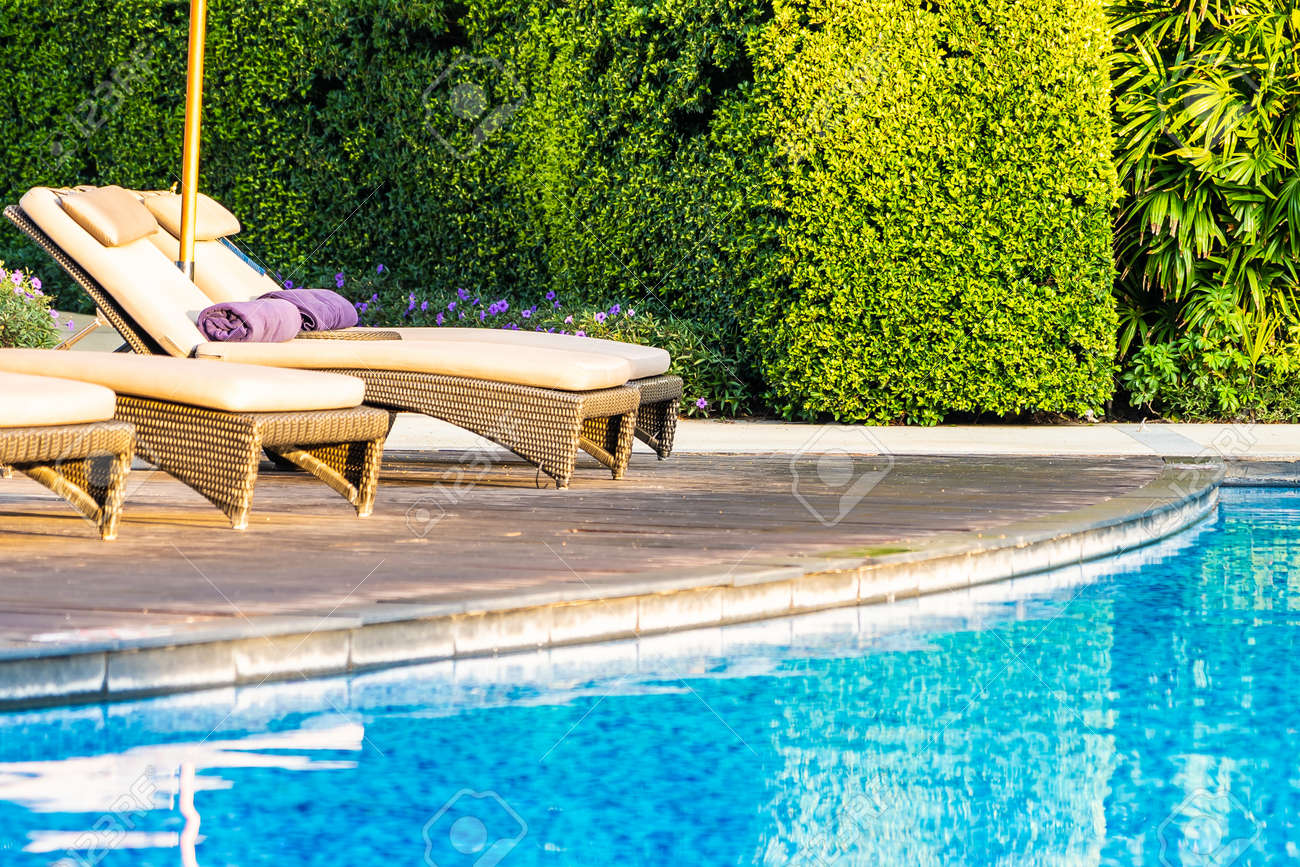 Beautiful outdoor swimming pool with bed deck chair and umbrella..