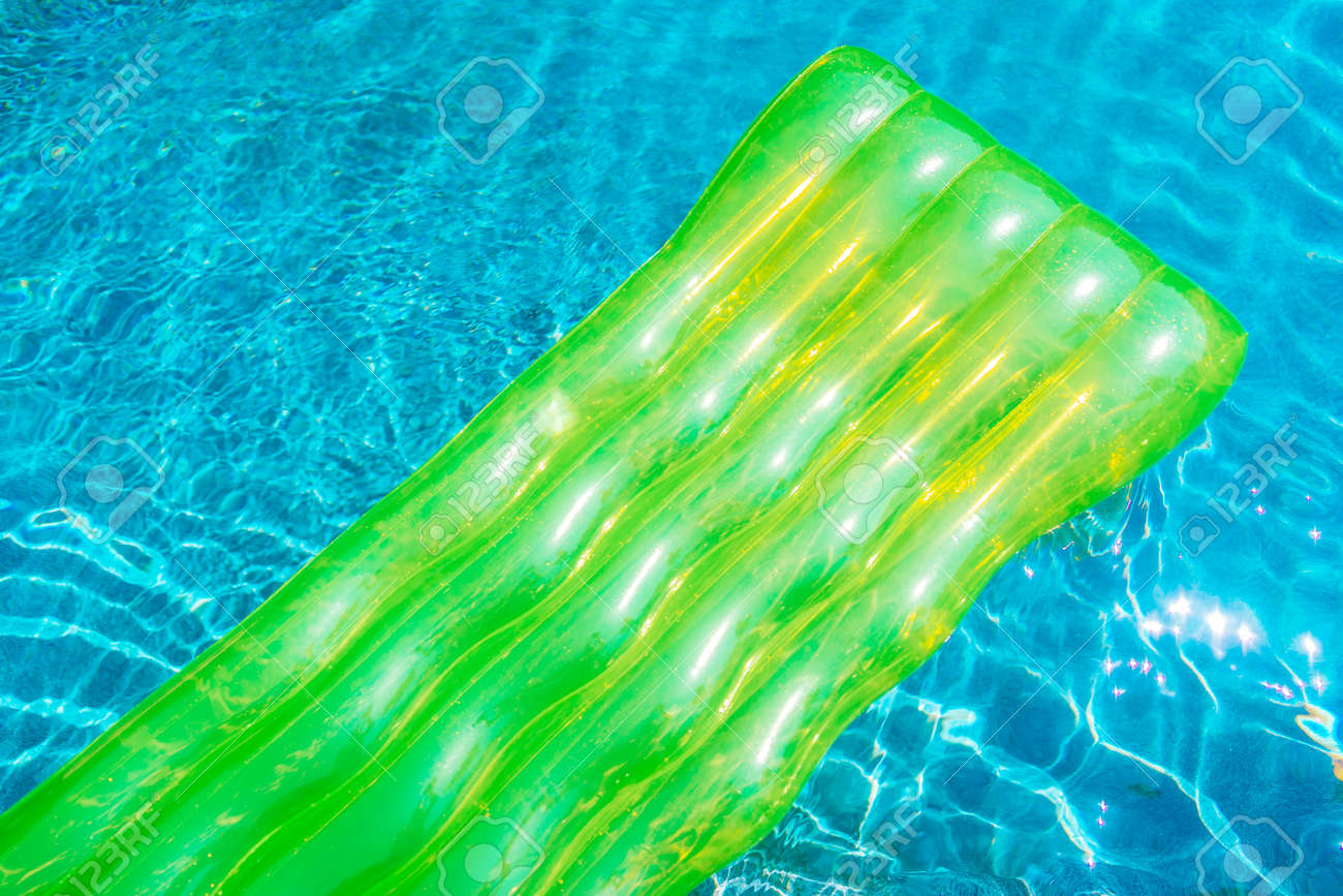 Colorful swim ring or rubber float around swimming pool water..