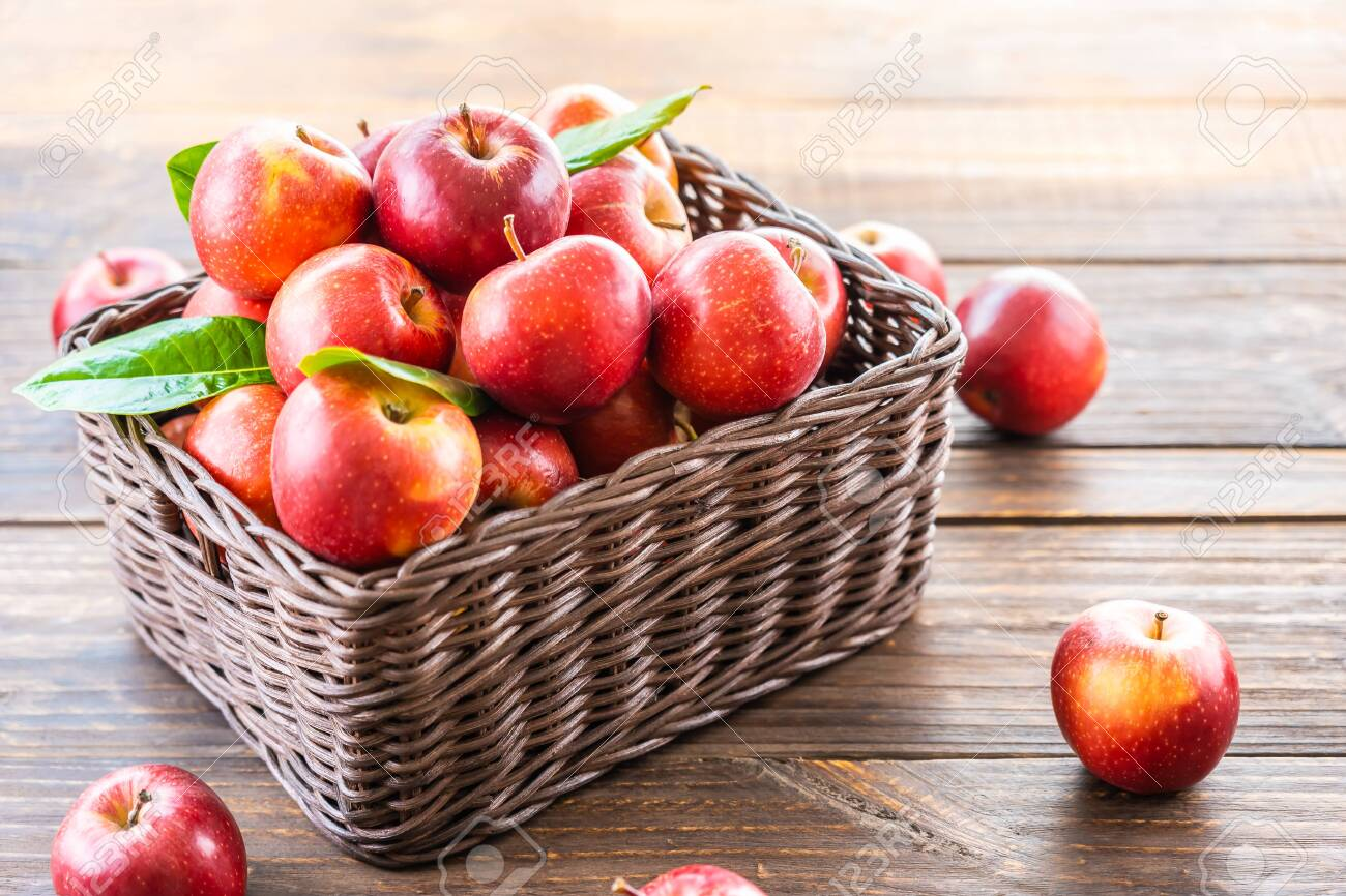 A lot of red apple fruit in brown basket on table - 131908802