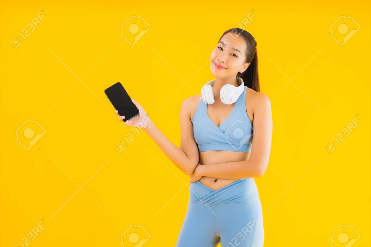 Portrait beautiful young asian woman wear sport wear with smart phone and headphone for listen music on yellow background - 151101176