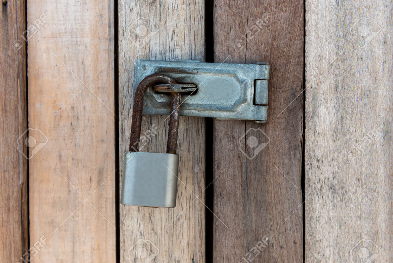 Close up of padlock and old metal hasp and staple on an old wooden door Stock & Close Up Of Padlock And Old Metal Hasp And Staple On An Old Wooden ...