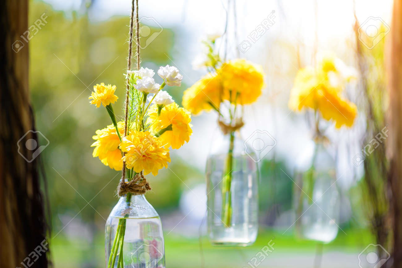 The Marigold Flowers In A Gl Bottle Hanging. Flower Vase ... on windchimes from bottles, glasses from bottles, lamps from bottles, garden art from bottles, bracelets from bottles, bird feeders from bottles,