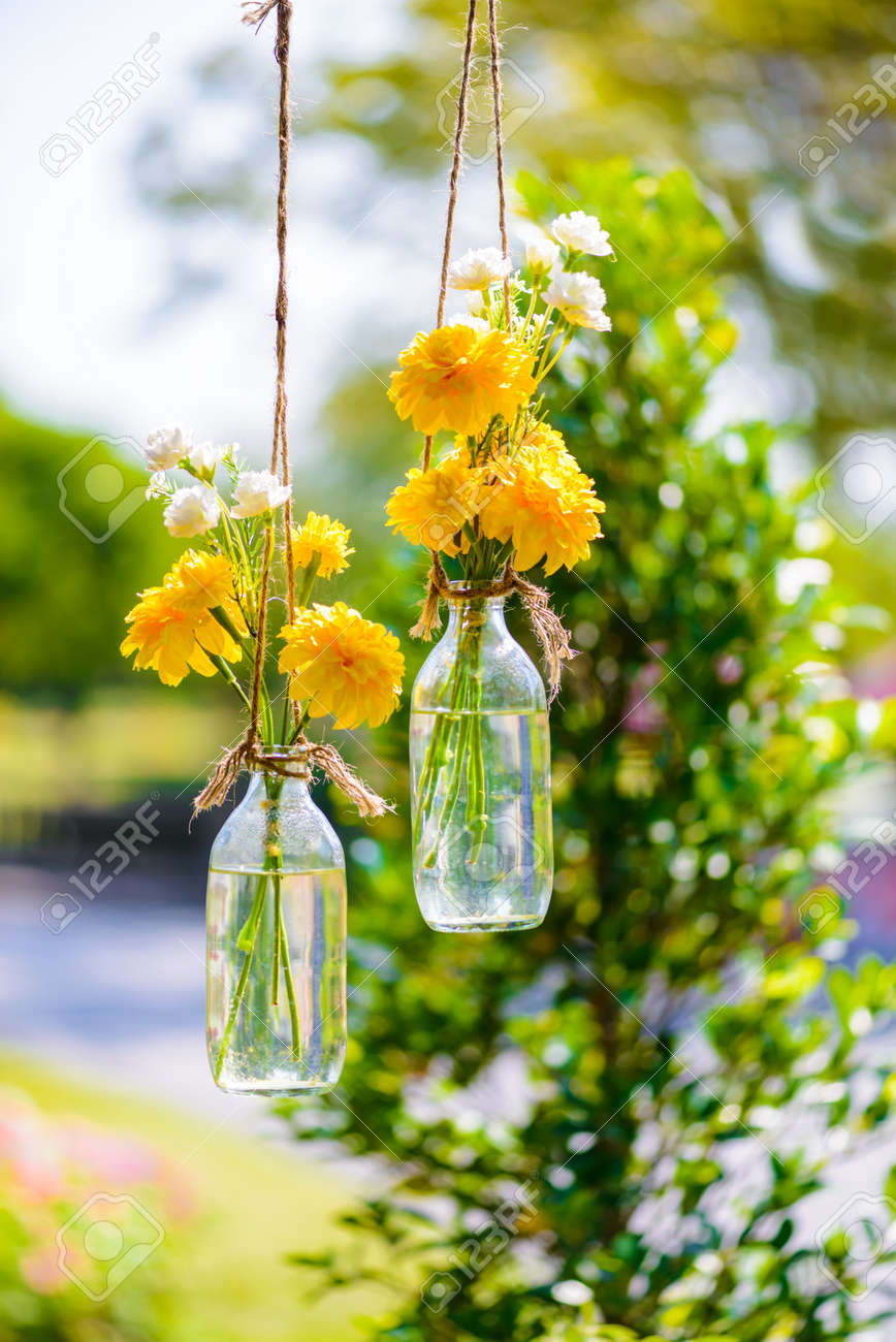 the marigold flowers in a glass bottle hanging flower vase