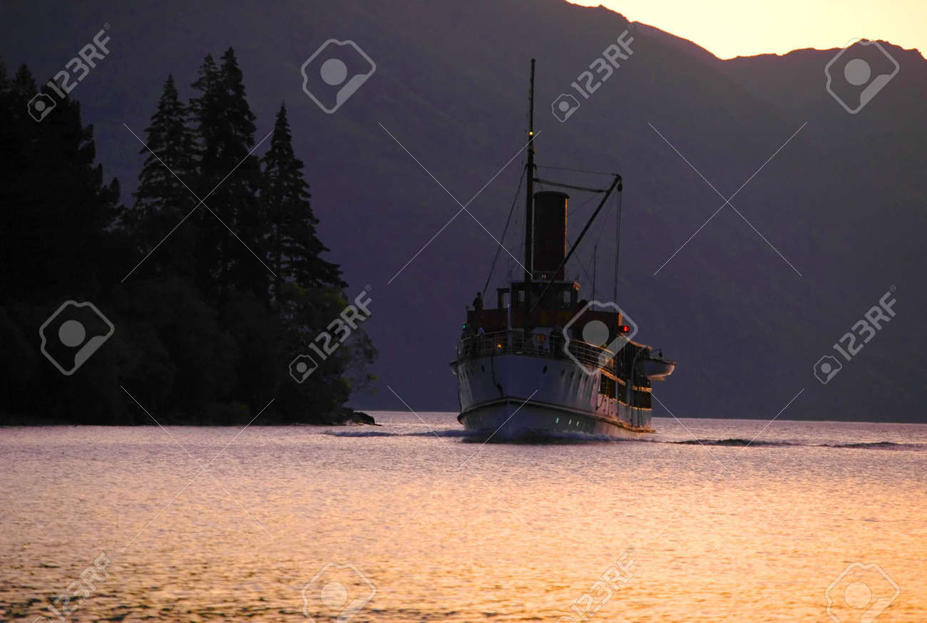 An old steamboat doing its job on mountain lake. Silhouettes of mountains and forest. Stock Photo - 1843584