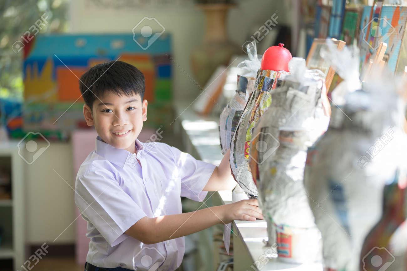 Glückliche asiatische kindshow sein handwerk und schauende kamera