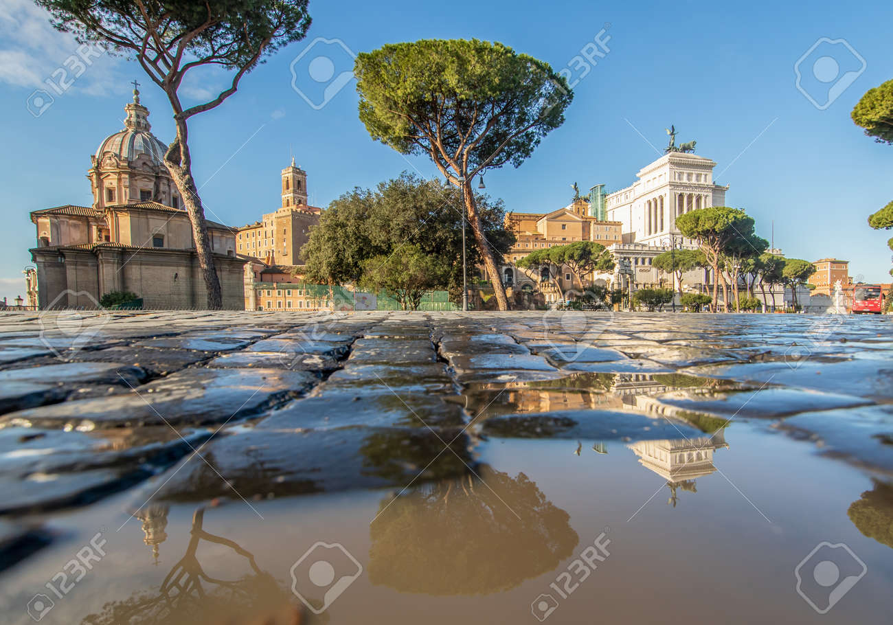 Rome, Italy - in Winter time, frequent rain showers create pools in which the wonderful Old Town of Rome reflect like in a mirror. Here in particular Via dei Fori Imperiali - 162676794