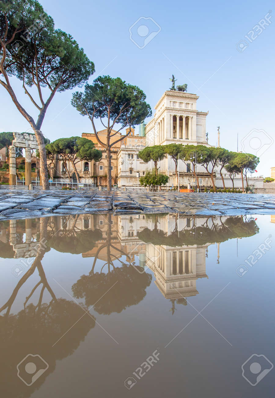 Rome, Italy - in Winter time, frequent rain showers create pools in which the wonderful Old Town of Rome reflect like in a mirror. Here in particular Via dei Fori Imperiali - 162969234