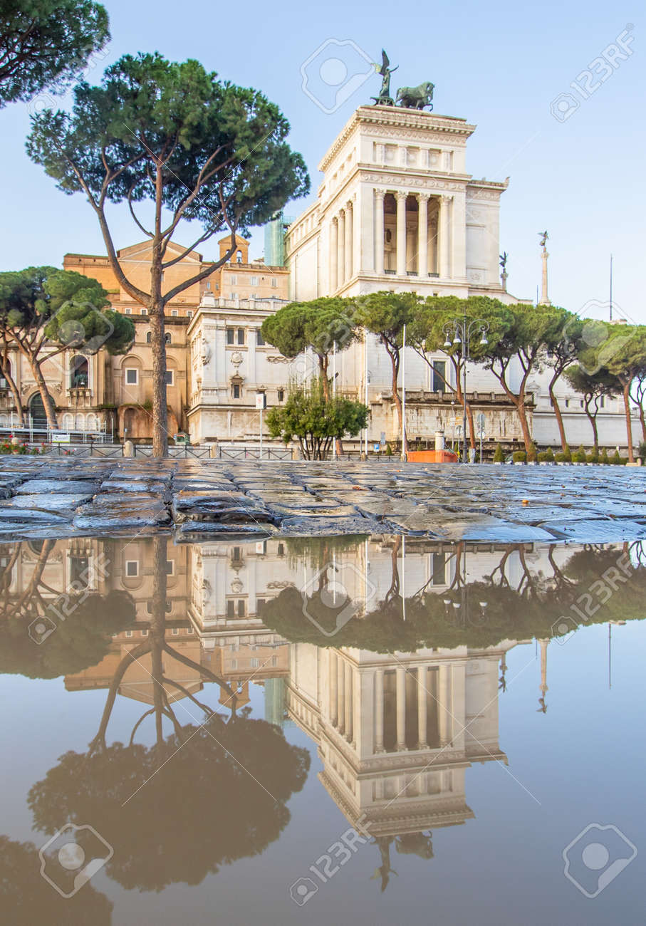 Rome, Italy - in Winter time, frequent rain showers create pools in which the wonderful Old Town of Rome reflect like in a mirror. Here in particular Via dei Fori Imperiali - 163155407