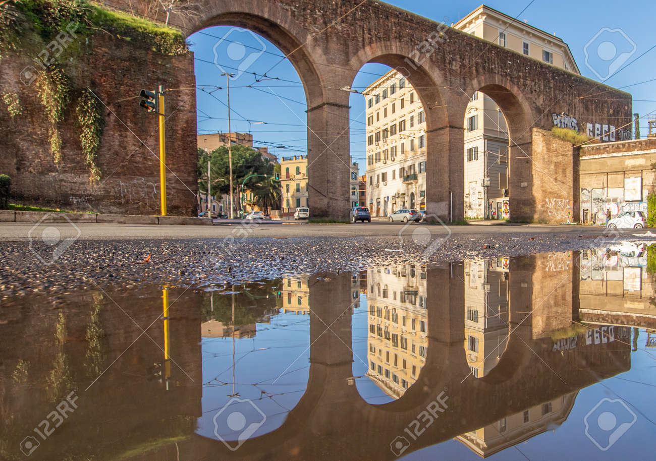 Rome, Italy - in Winter time, frequent rain showers create pools in which the wonderful Old Town of Rome reflect like in a mirror. Here in particular Piazza di Porta Maggiore - 163759480