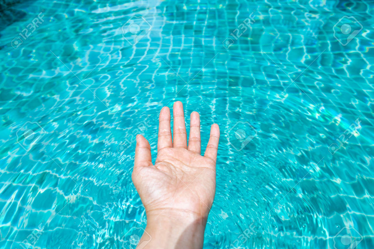 Girl bare hand over clean and crystal clear swimming pool water..