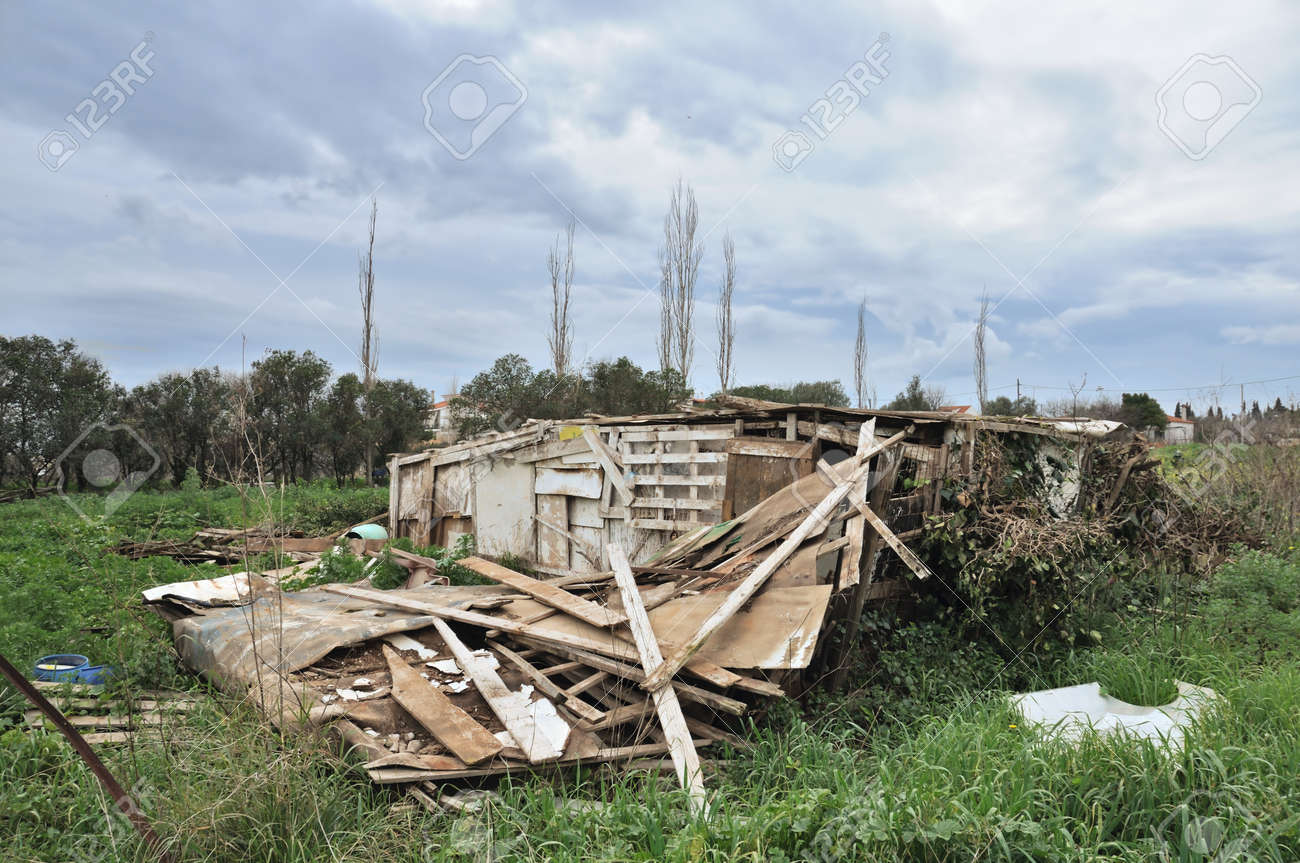 Collapsed wooden hut ruins and overcast sky. Stock Photo - 8735480