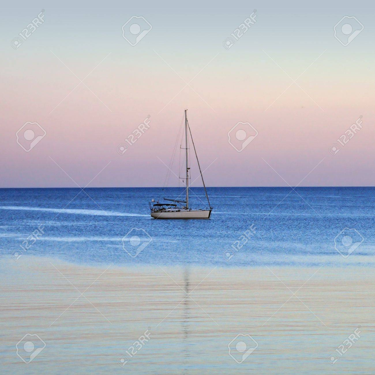 Sailboat reflections on sea water. Sunset sea and sky horizon. Stock Photo - 9217193