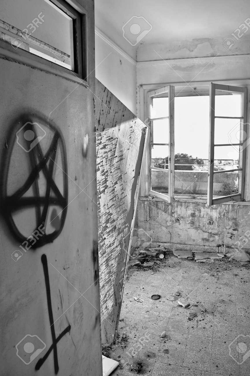 Satanic symbols graffiti on the door of an abandoned house. Black and white. Stock Photo - 9316245