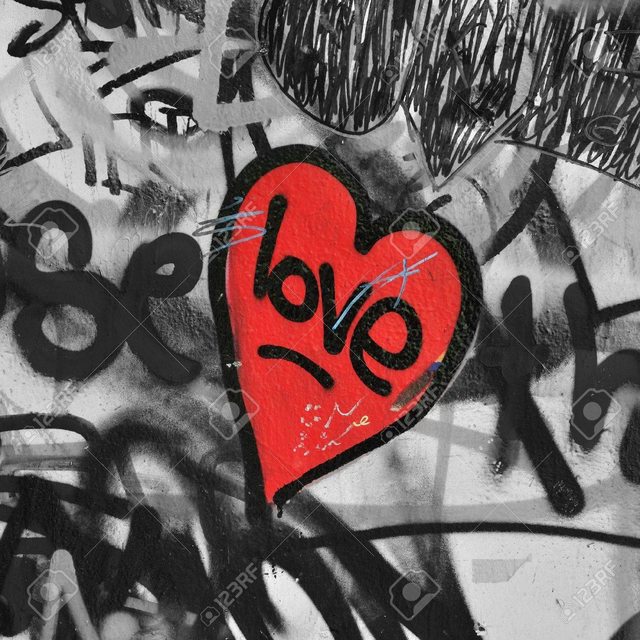 Red painted love heart on graffiti covered black and white wall background  Selective saturation  Stock Photo - 13538022