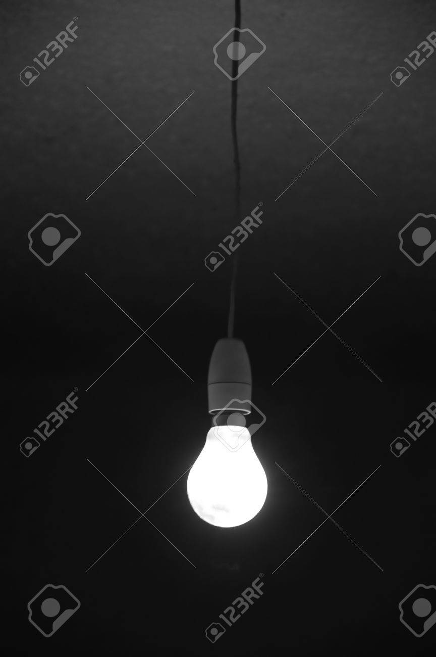 Dark room with light bulb - Incandescent Bare Light Bulb Glowing In Dark Room Abstract Background Stock Photo 17122194