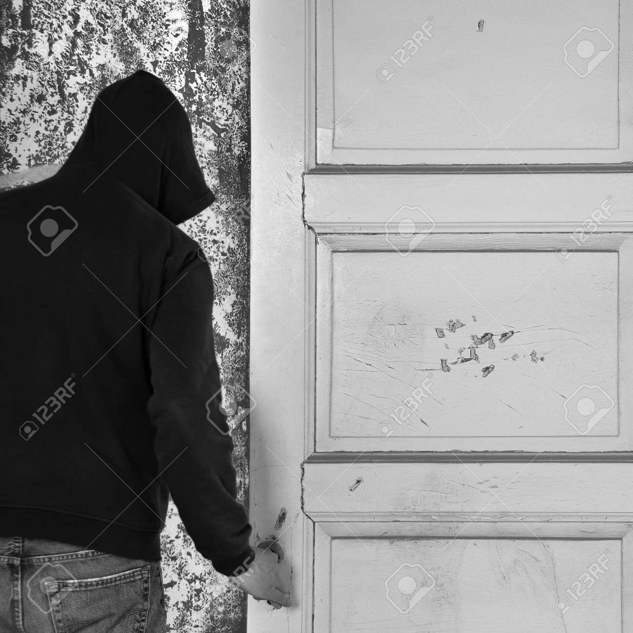 Hooded figure exiting through the door of an abandoned house. Stock Photo - 17107579