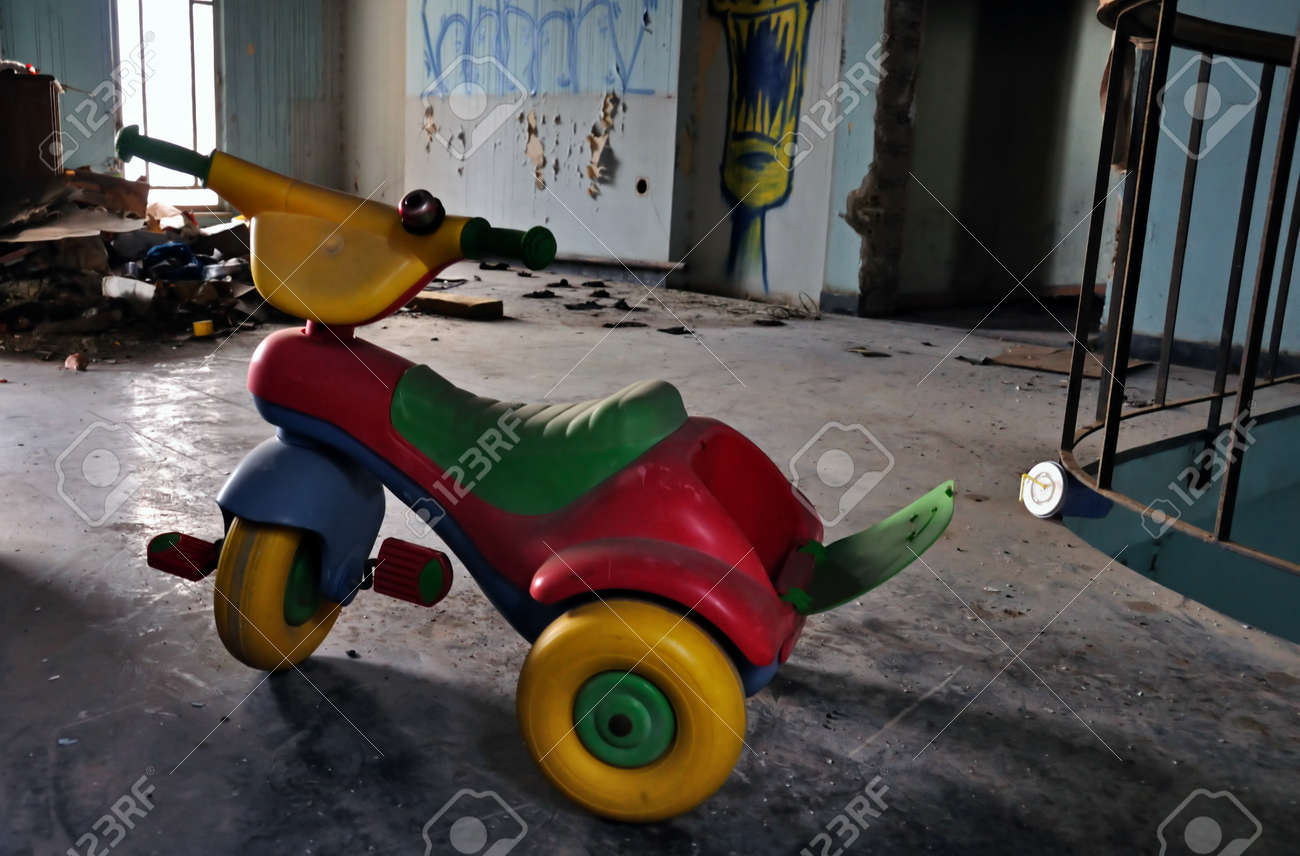Little kids tricycle toy bike in abandoned house decayed interior. Social issues. Stock Photo - 17932472