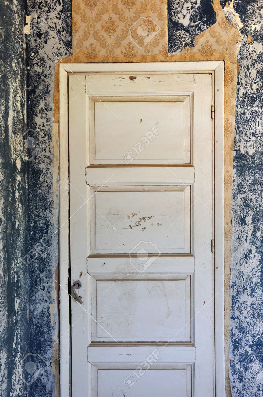 Shut wooden door peeling wall and torn vintage wallpaper in abandoned house. Stock Photo - & Shut Wooden Door Peeling Wall And Torn Vintage Wallpaper In ... Pezcame.Com