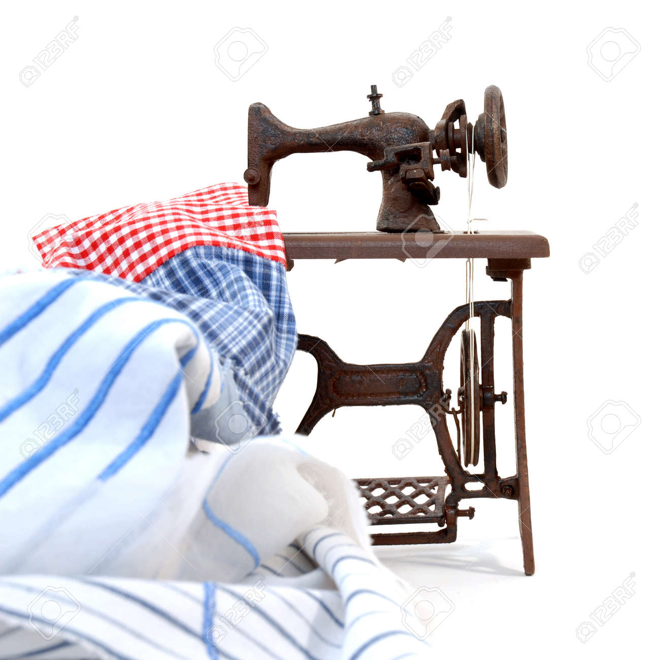 An old sewing machine with colours frabrics on a white background Stock Photo - 8772248