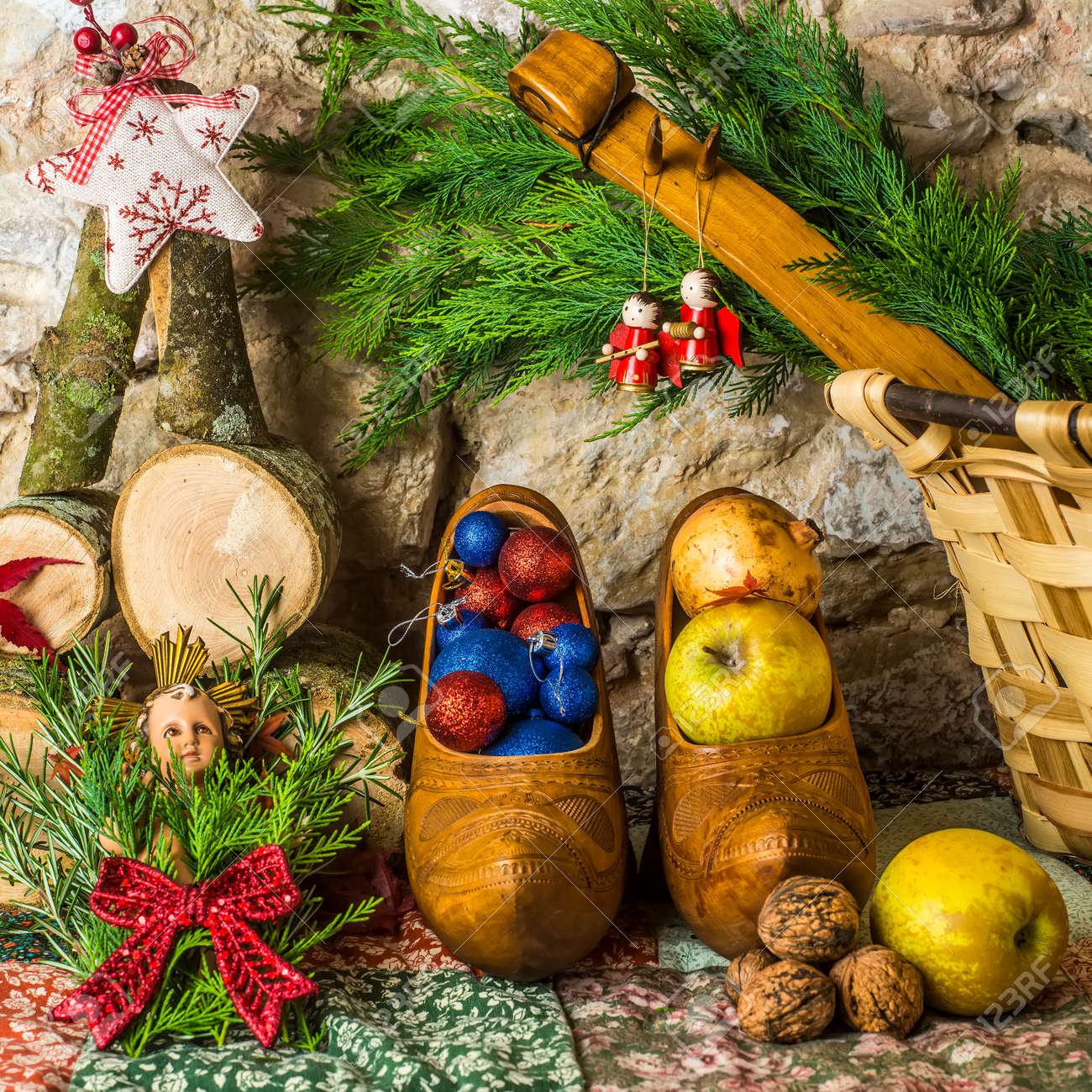baby jesus christmas cardvariety of christmas decorations and wicker basket with spruce on stonewall