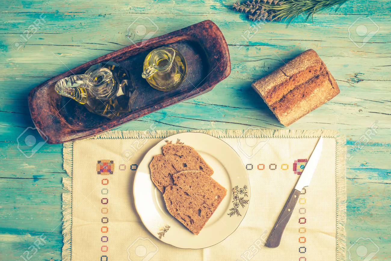 Olive oil and bread on a wooden table, Mediterranean diet, healthy
