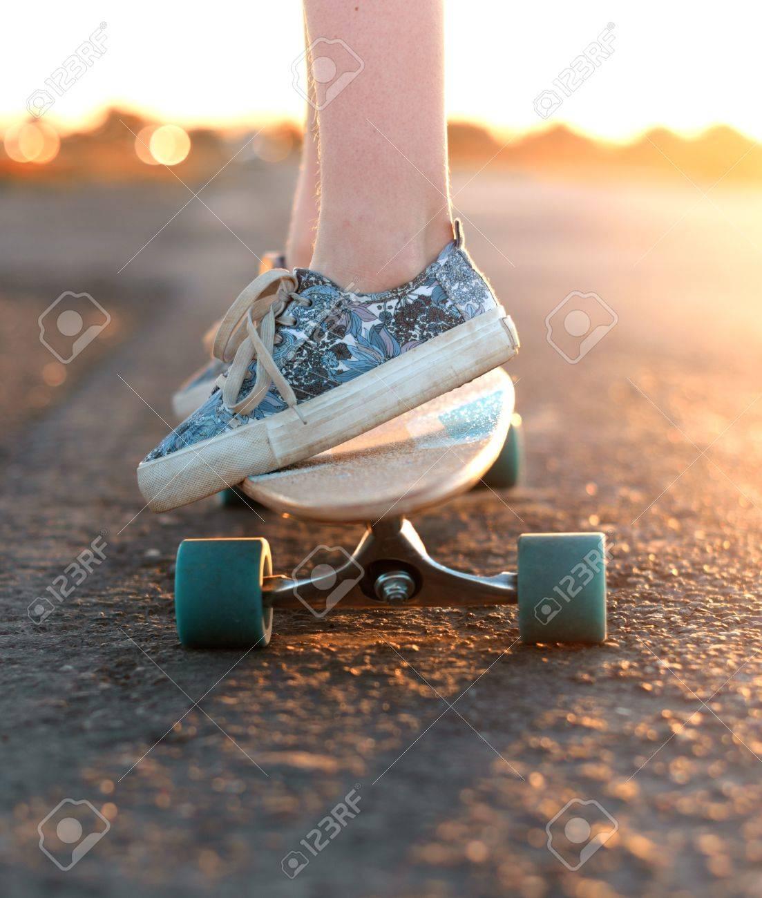 Teenager cavalca un longboard sulla strada Archivio Fotografico - 56212232