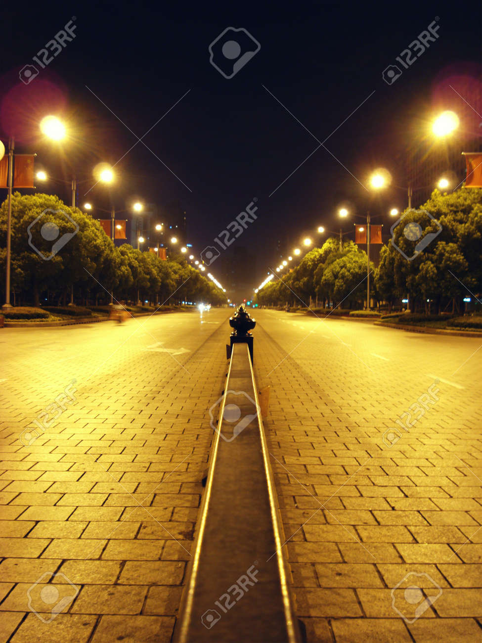almost deserted street in the middle of the park in Shanghai People Square lit by streetlamps Stock Photo - 10467282