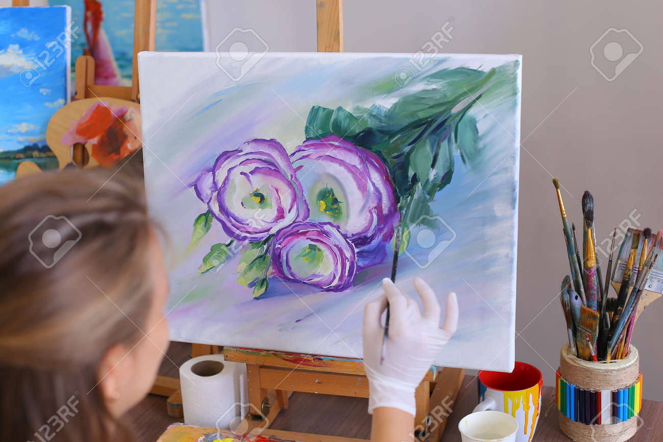 Artist paints on white canvas beautiful purple flowers with green