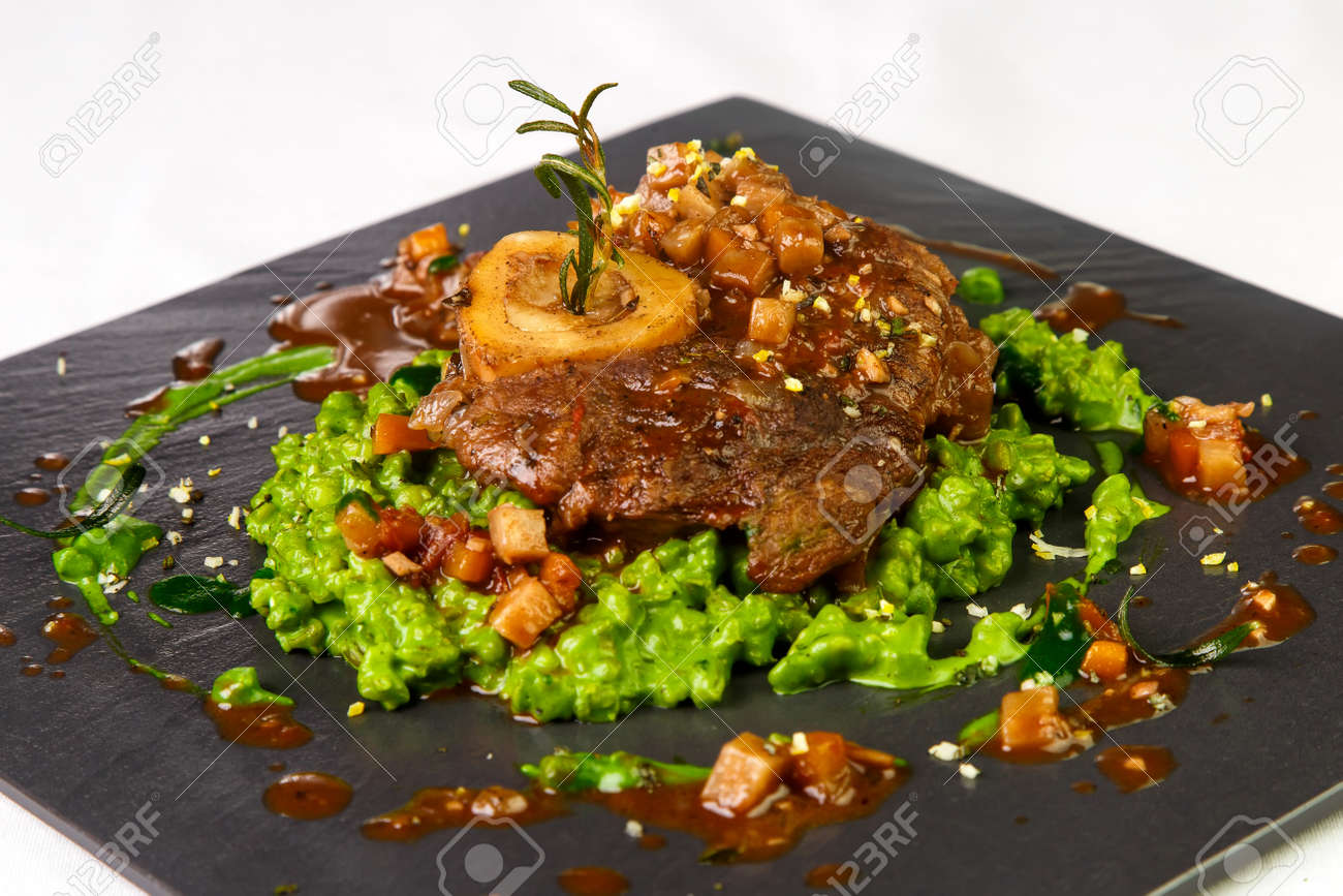 Juicy piece of pork meat on green side dish and with sauce on