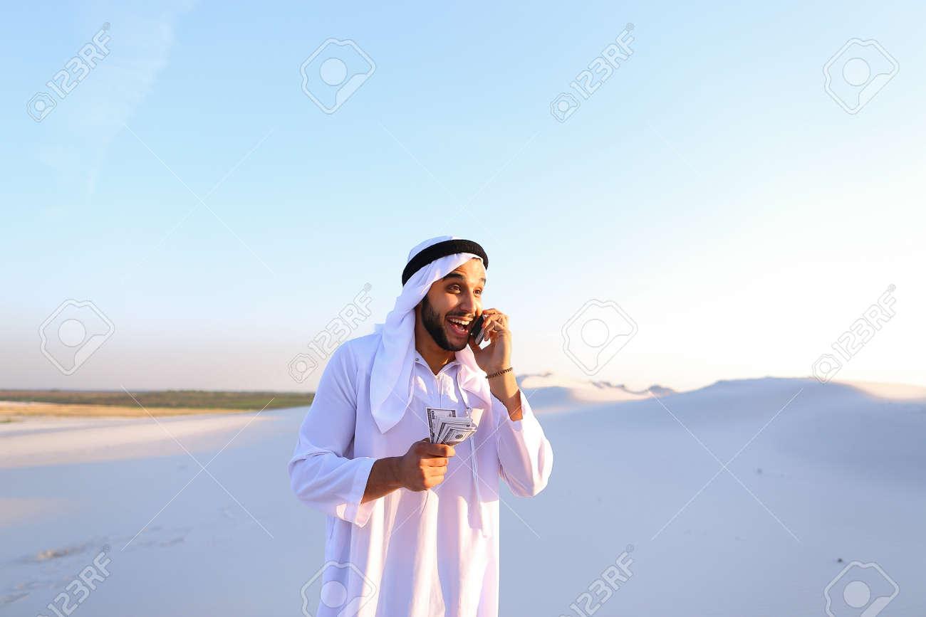 Joven árabe Llama A Un Amigo O Socio De Negocios Y Con Una Sonrisa