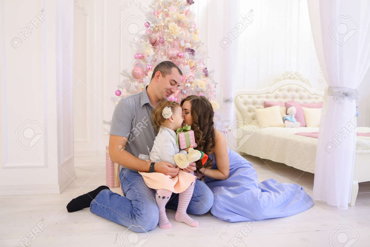 Beautiful young husband and wife play laugh and tickle daughter sitting on floor against backdrop of christmas ornaments on tree