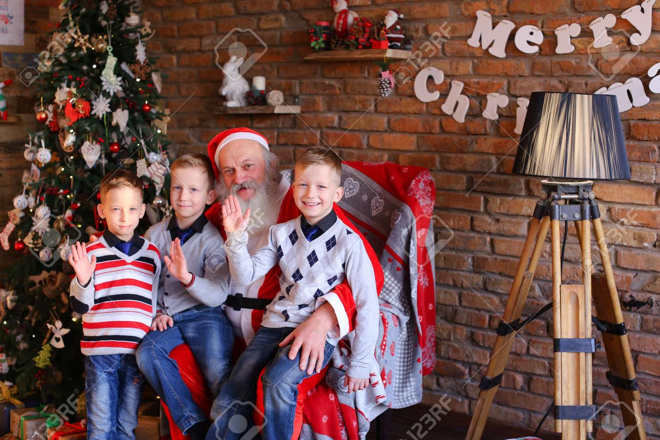 Little Wonderful Male Children Sit On Their Knees Near Santa.. Stock ...