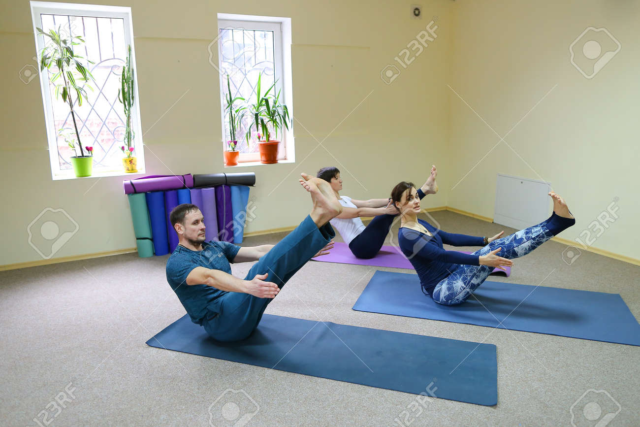 Two Women And Men Of American Appearance Engaged In Yoga People