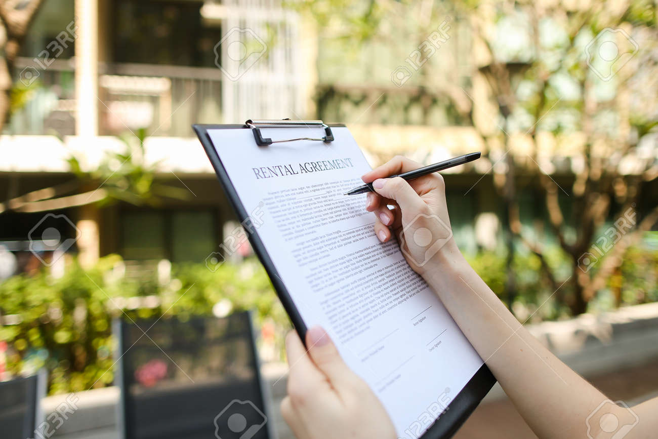 Close Up Portrait Of Woman Hands Signing Rental Agreement On