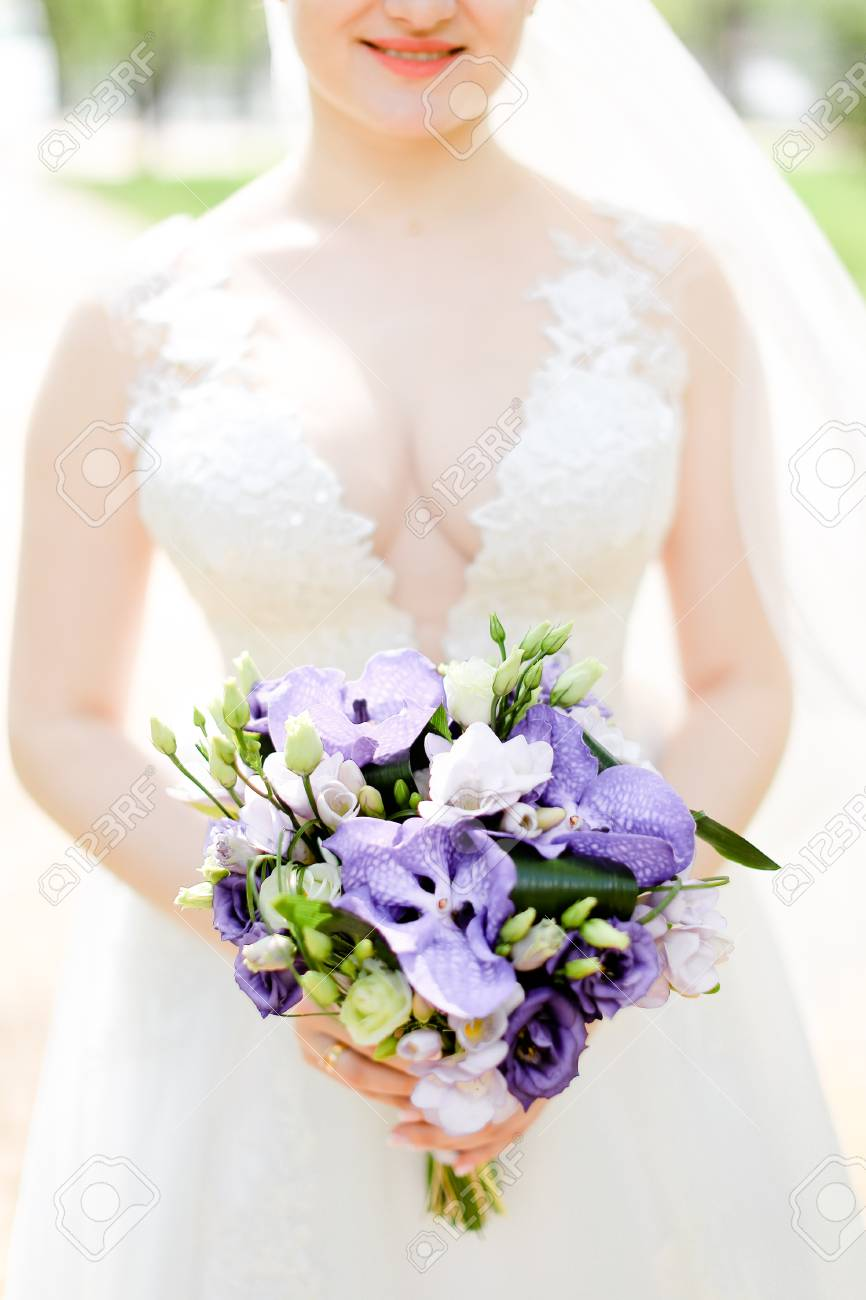 Aucasian Happy Young Bride Keeping Bouquet Of Flowers And Wearing