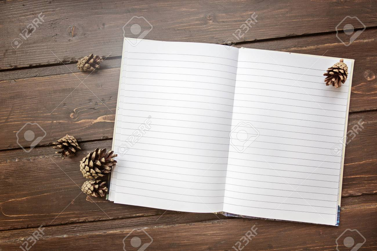 Stock Photo   Top Image Of Open Notebook With Blank Pages, Next To Pine  Cones Over Wooden Table. Flat Lay Style